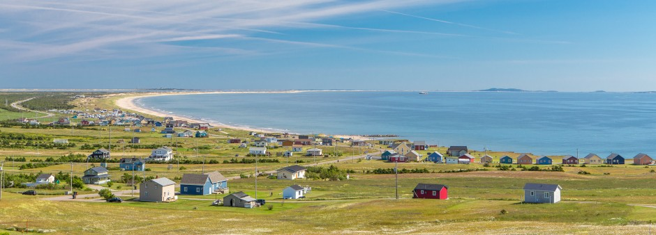 Magdalen Island, colored houses, blue sky, sea, beach